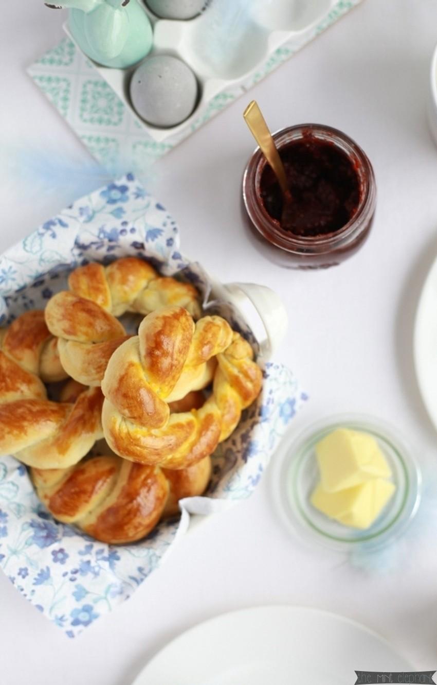 Hefekränze auf Ostertafel mit Marmelade und Butter