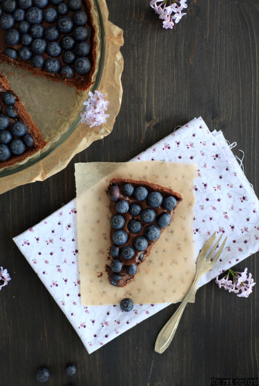 Schokoladen-Heidelbeer-Tarte-Stück-von-oben-auf-lila-stoffps